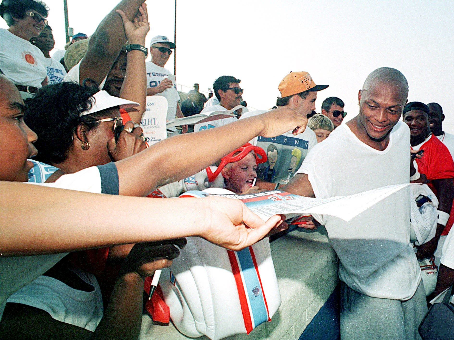 Tennessee Oilers running back Eddie George is mobbed by excited fans as he signed autographs following the Oilers first practice in Nashville at Tennessee State University July 19, 1997.