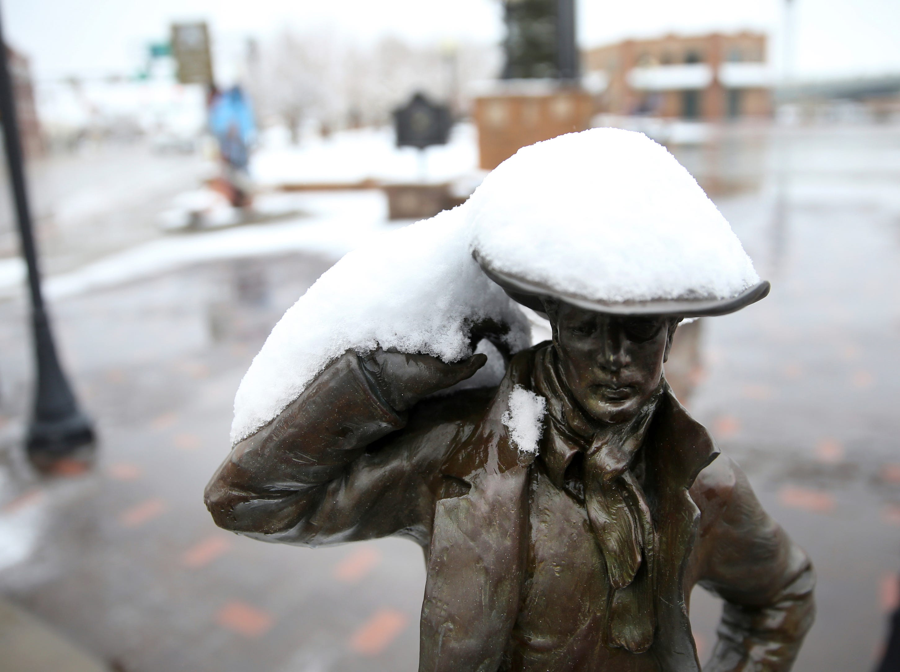 "Snow rests on the brim of the cowboy hat on the sculpture ""Buster"" by Bobby Carlyle in the Cheyenne Depot Plaza after initial snowfall and before a blizzard warning went into effect for southeast Wyoming on Wednesday, April 10, 2019, in Cheyenne. The storm was bringing snow to an area stretching from Colorado and into Montana."