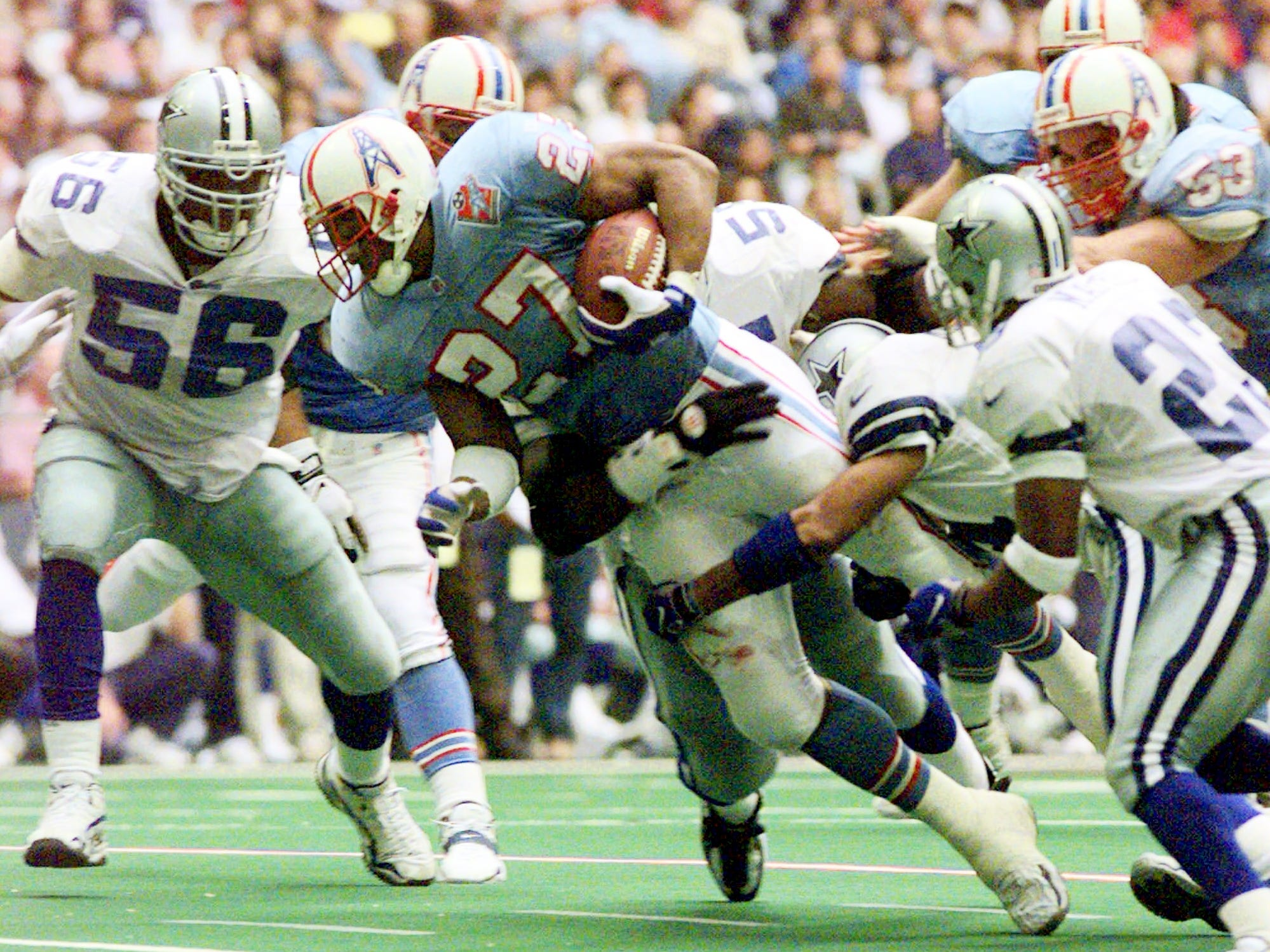 Tennessee Oilers running back Eddie George (27) is tackled by Cowboys safety Brock Marion (31) after picking up a first down in the second quarter Nov. 27, 1997 in Irving, Texas. The Oilers won, 27-14.