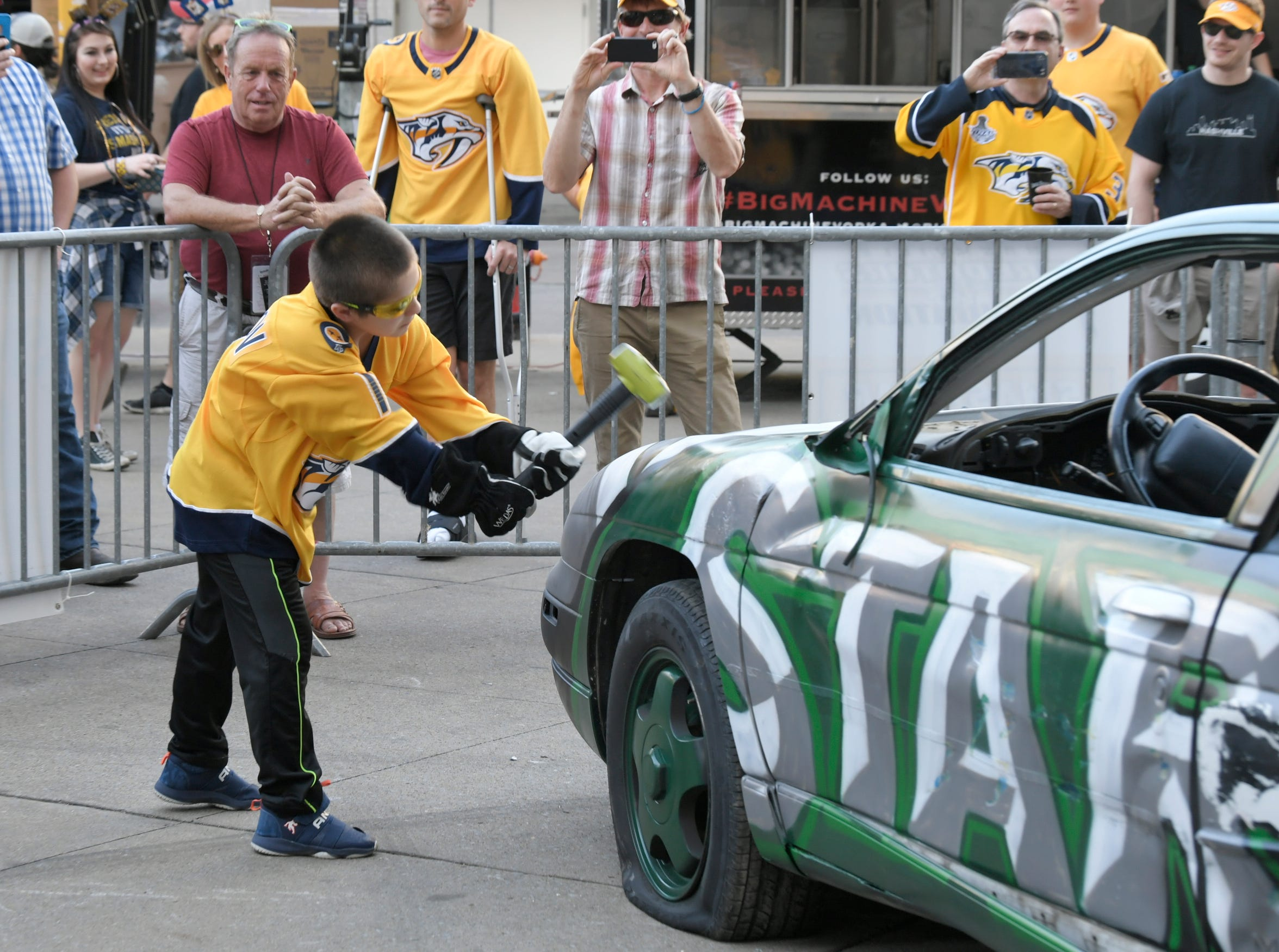 Branson Hughes, 10, of Lebanon, takes a whack at the Predators' smash car before the divisional semifinal game at Bridgestone Arena in Nashville, Tenn., Wednesday, April 10, 2019.