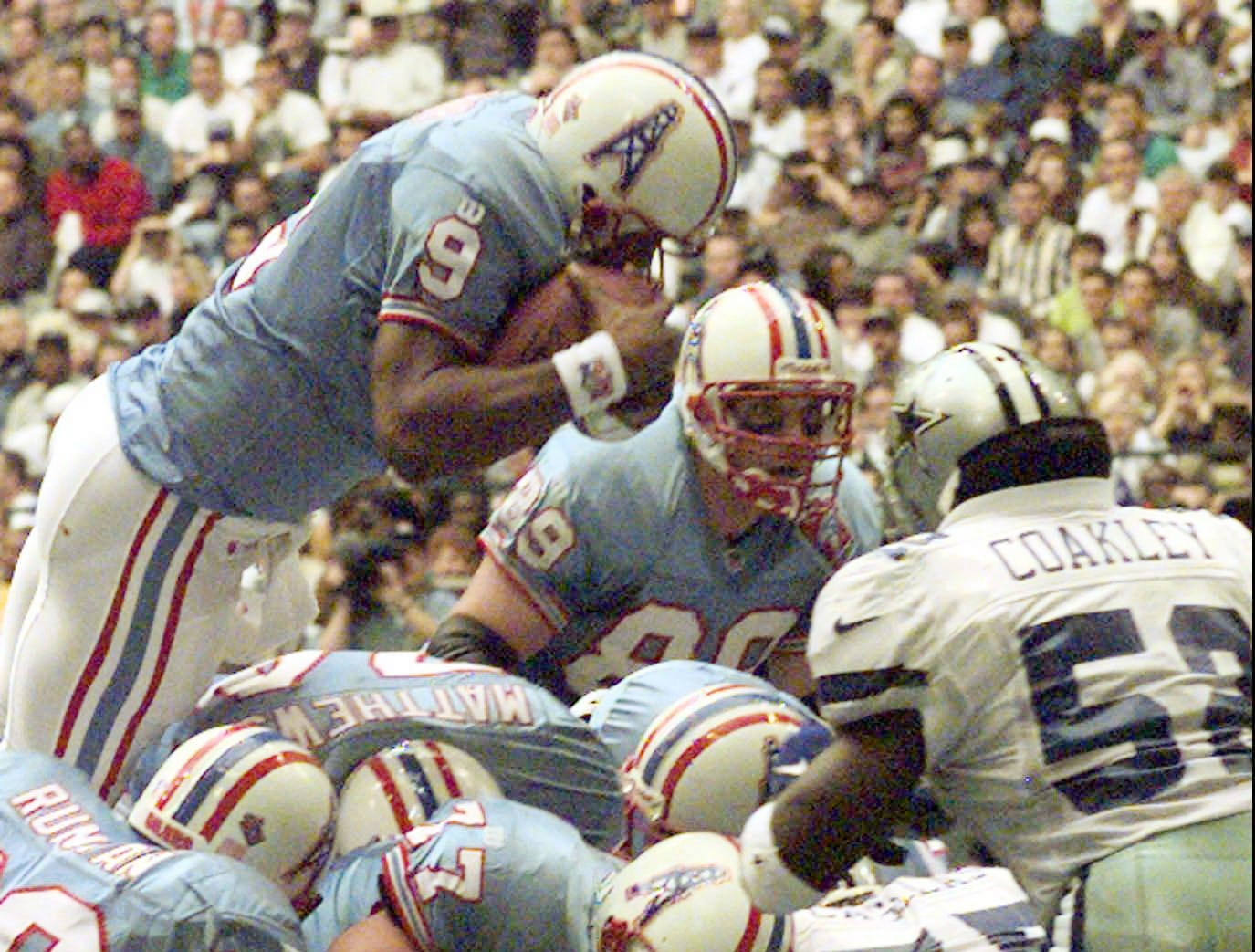 Tennessee Oilers quarterback Steve McNair (9), jumps over the heap to score a touchdown against the Dallas Cowboys during the first quarter of their Thanksgiving game Nov. 27, 1997 in Irving, Texas.