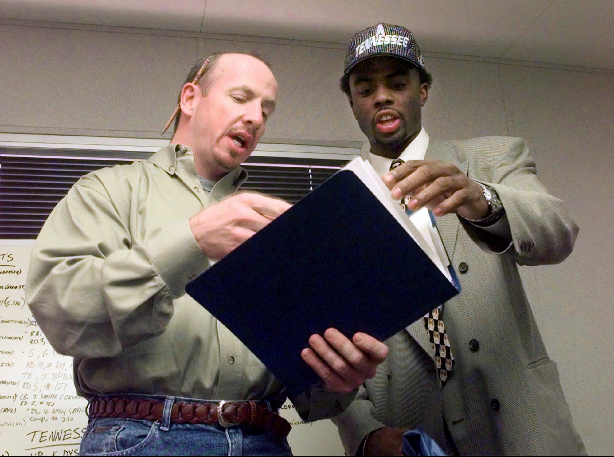 Kevin Dyson, right, the first-round draft pick of the Tennessee Oilers, gets his strength and conditioning book from Oilers strength coach Steve Watterson in Nashville April 19, 1998. Dyson is a wide receiver from Utah.
