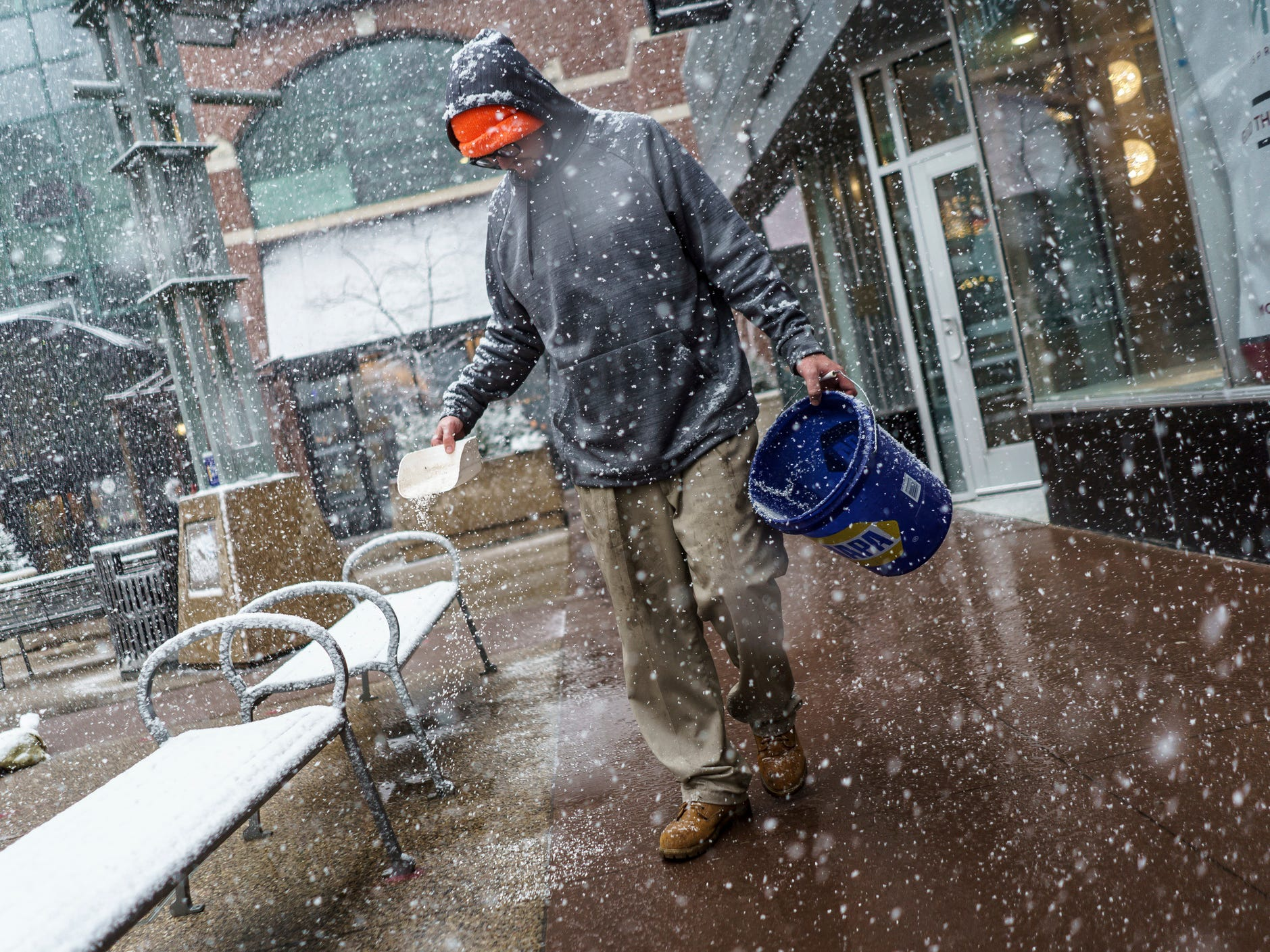 Joshua Carpenter, with Meyer Outdoor Services, sprinkles salt on Peace Plaza sidewalk as snow falls Wednesday, April 10, 2019, in Rochester, Minn.