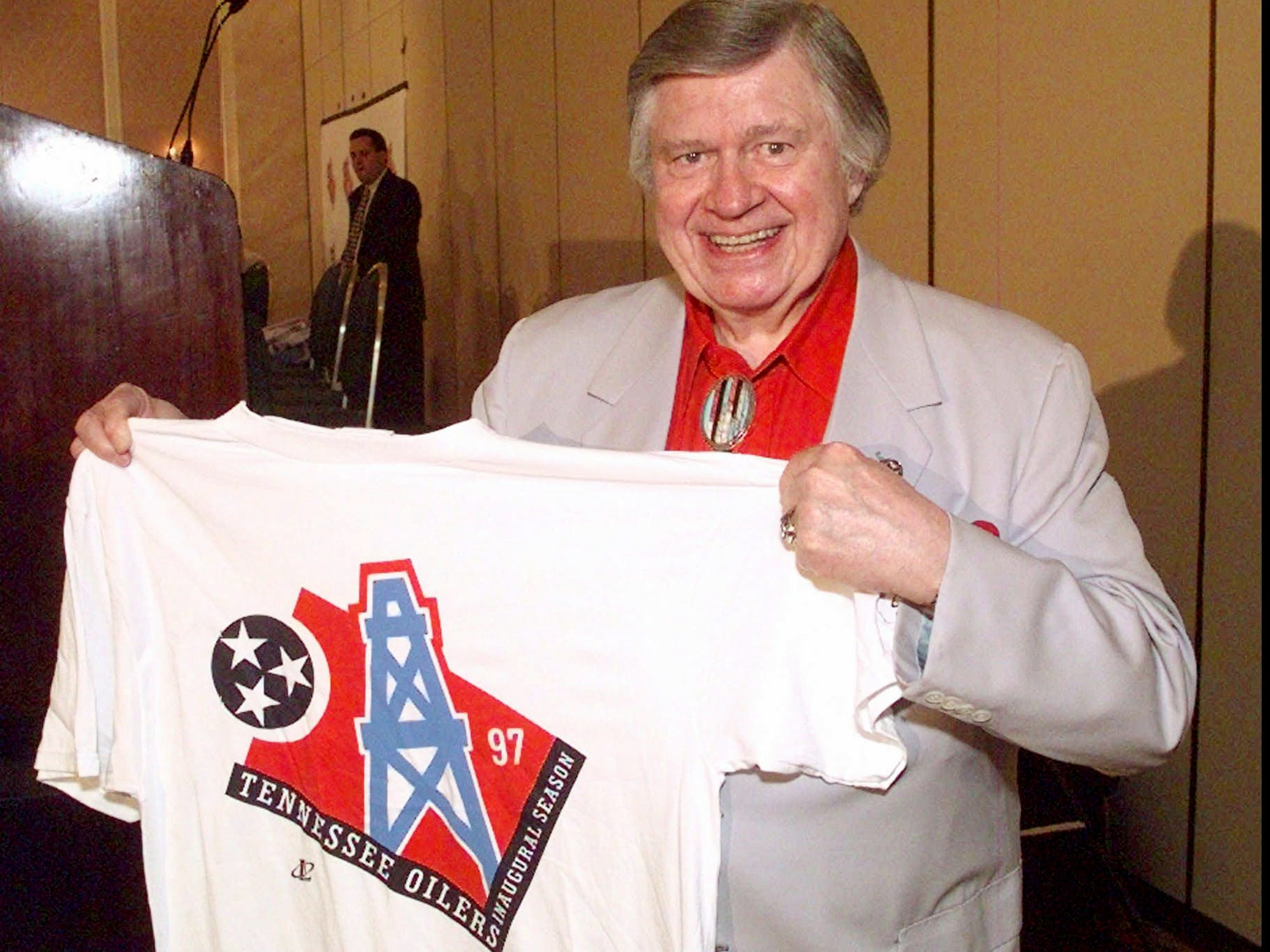 Houston Oilers owner Bud Adams shows off a T-shirt with the new logo the team will use this season when it moves to Tennessee. The logo was unveiled in Nashville during a press conference June 12, 1997. The plan is for the team to play two years in Memphis while its Nashville stadium is being built.