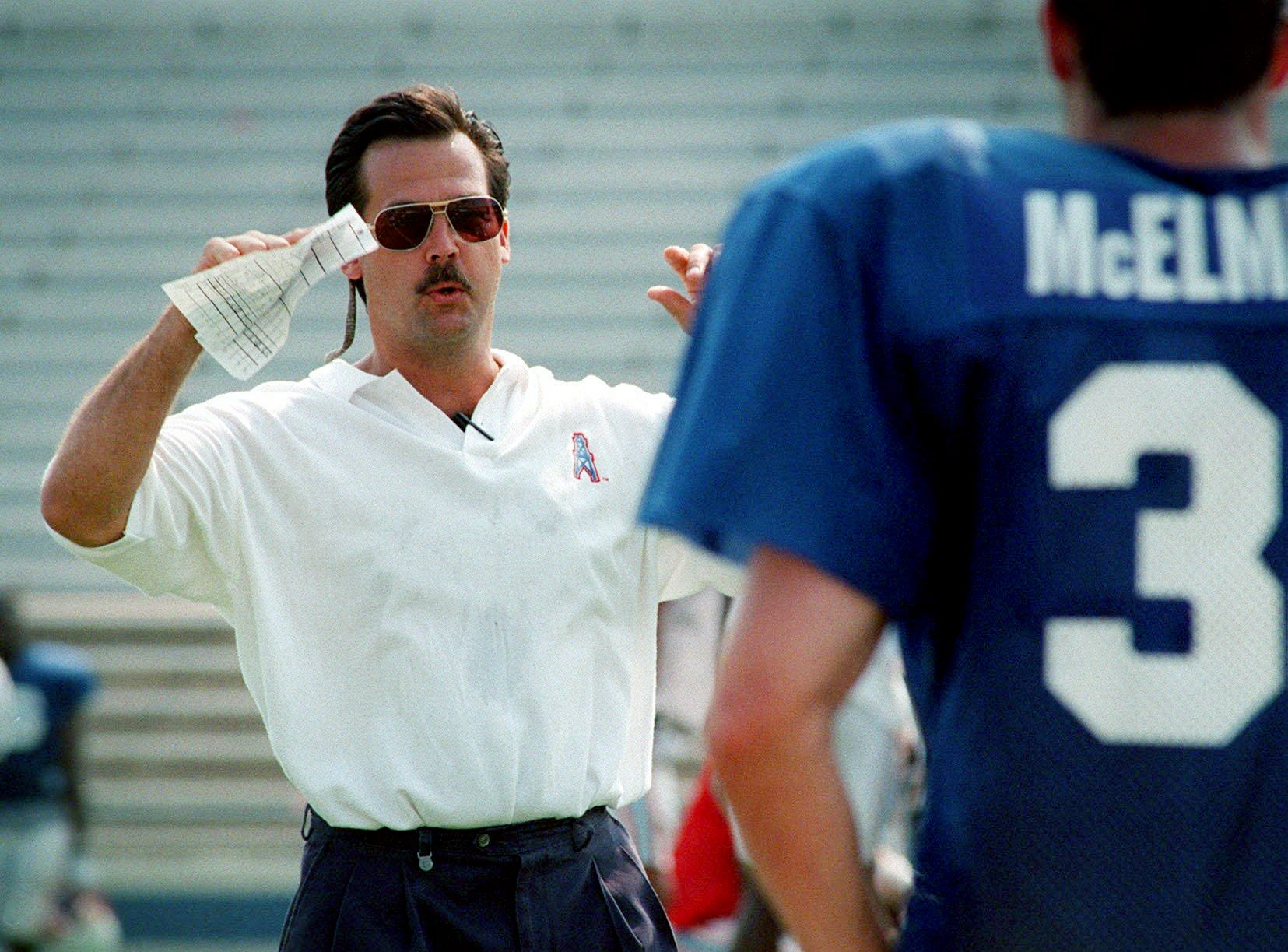 Tennessee Oilers head coach Jeff Fisher goes over a play with defensive players during practice at Tennessee State University July 29, 1997.
