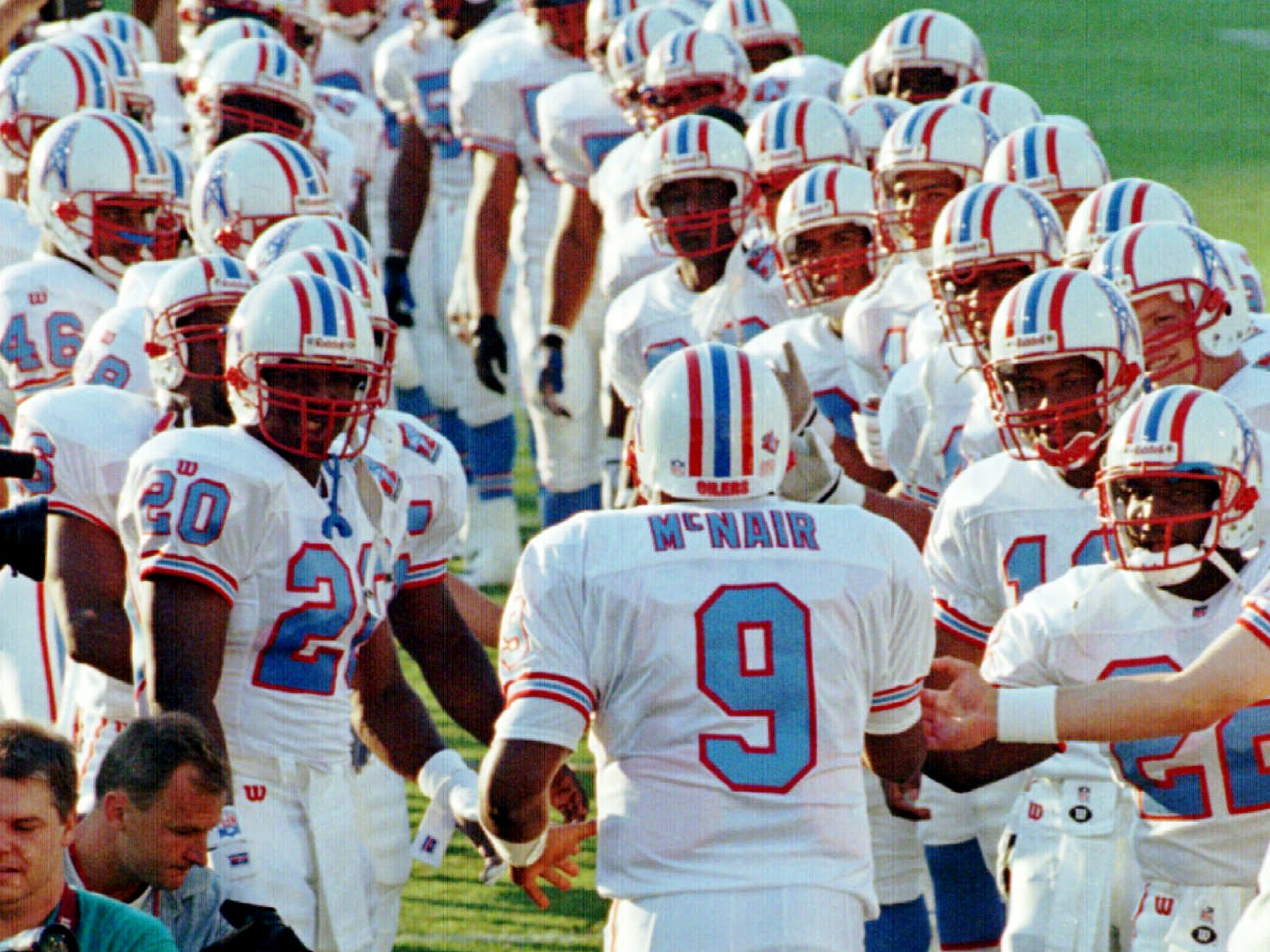 Tennessee Oilers quarterback Steve McNair (9) runs through a tunnel formed by his teammates as he is introduces before the team's first game in their new state, a pre-season game Aug. 2, 1997. The Oilers are playing the New Orleans Saints in Memphis, where they will play their first two seasons before moving into their new stadium in Nashville.