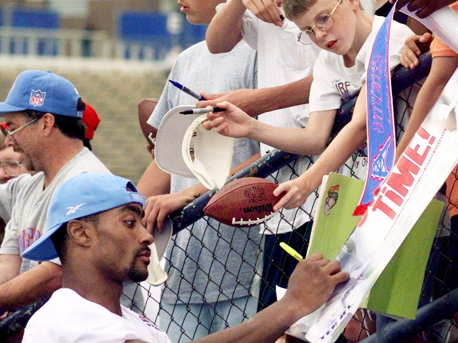 Tennessee Oilers wide receiver Yancey Thigpen, left, signs autographs for fans after practice Aug. 12, 1998 in Nashville.
