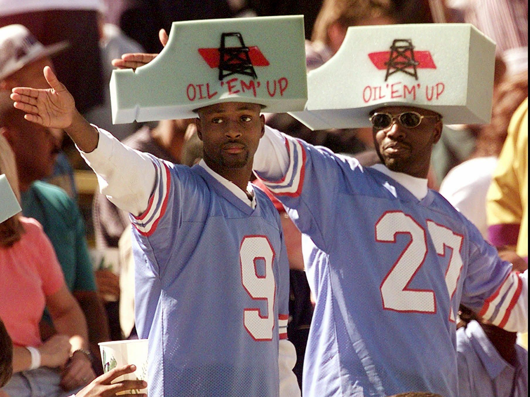 Two Tennessee Oilers fans signal an Oilers' first down during their 28-14 win over the Washington Redskins in Memphis Oct. 19, 1997. The Oilers drew 31,042 fans for the game, the largest crowd they've had this season at a home game.