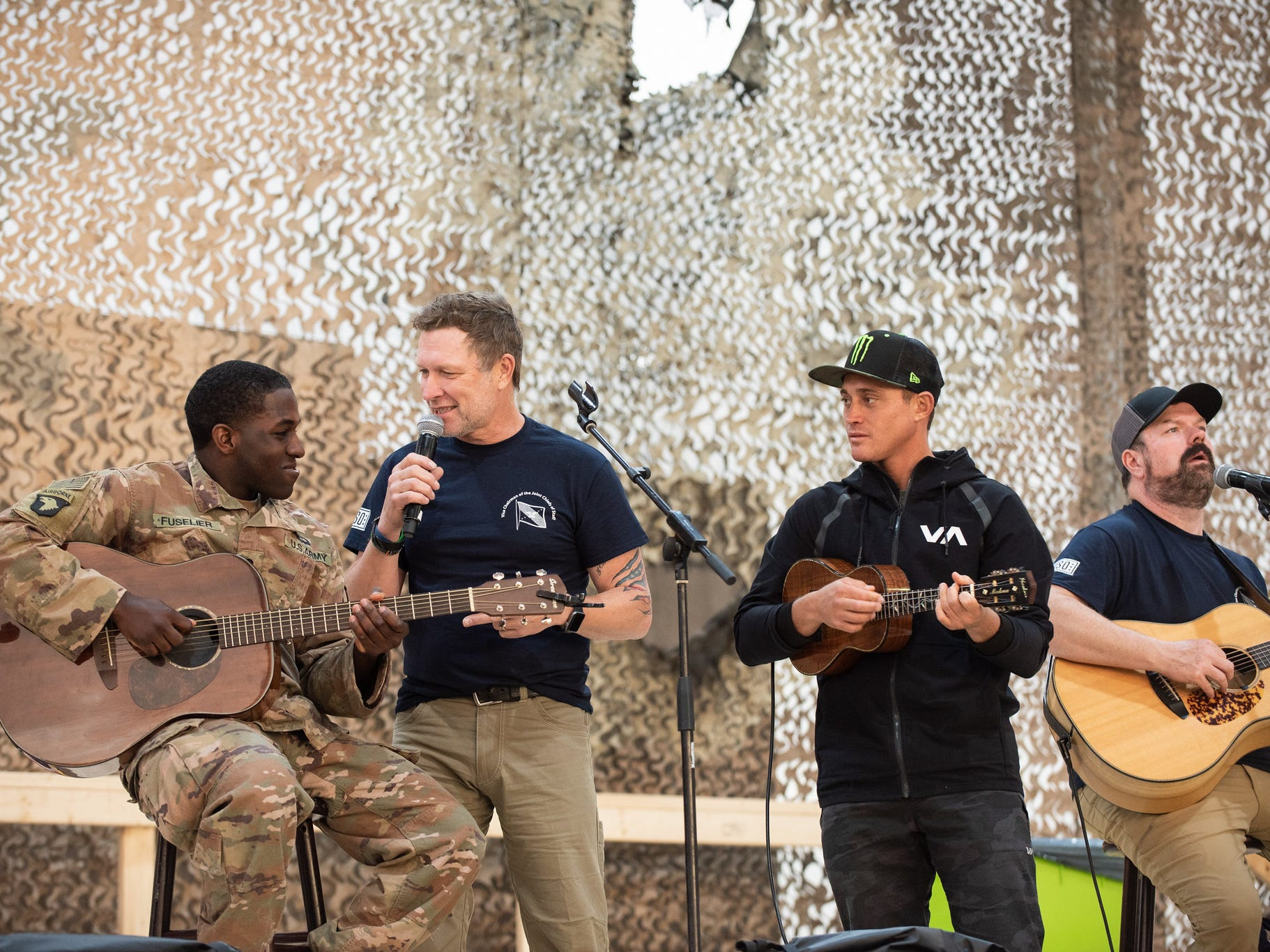 Country music artist Craig Morgan, with microphone, talks with a military member guitar player during a USO Show at Al Asad Airbase, Iraq; the sixth stop on the annual Vice Chairman's USO Tour, April 2.