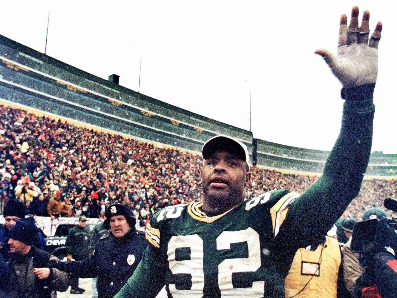 Green Bay Packers' Reggie White waves to the crowd as he walks around the field after the Packers' game against the Tennessee Oilers Dec. 20, 1998 in Green Bay, Wis. The game is likely White's last at Lambeau Field, since he has stated his intention to retire after the season. The Packers won 30-22.