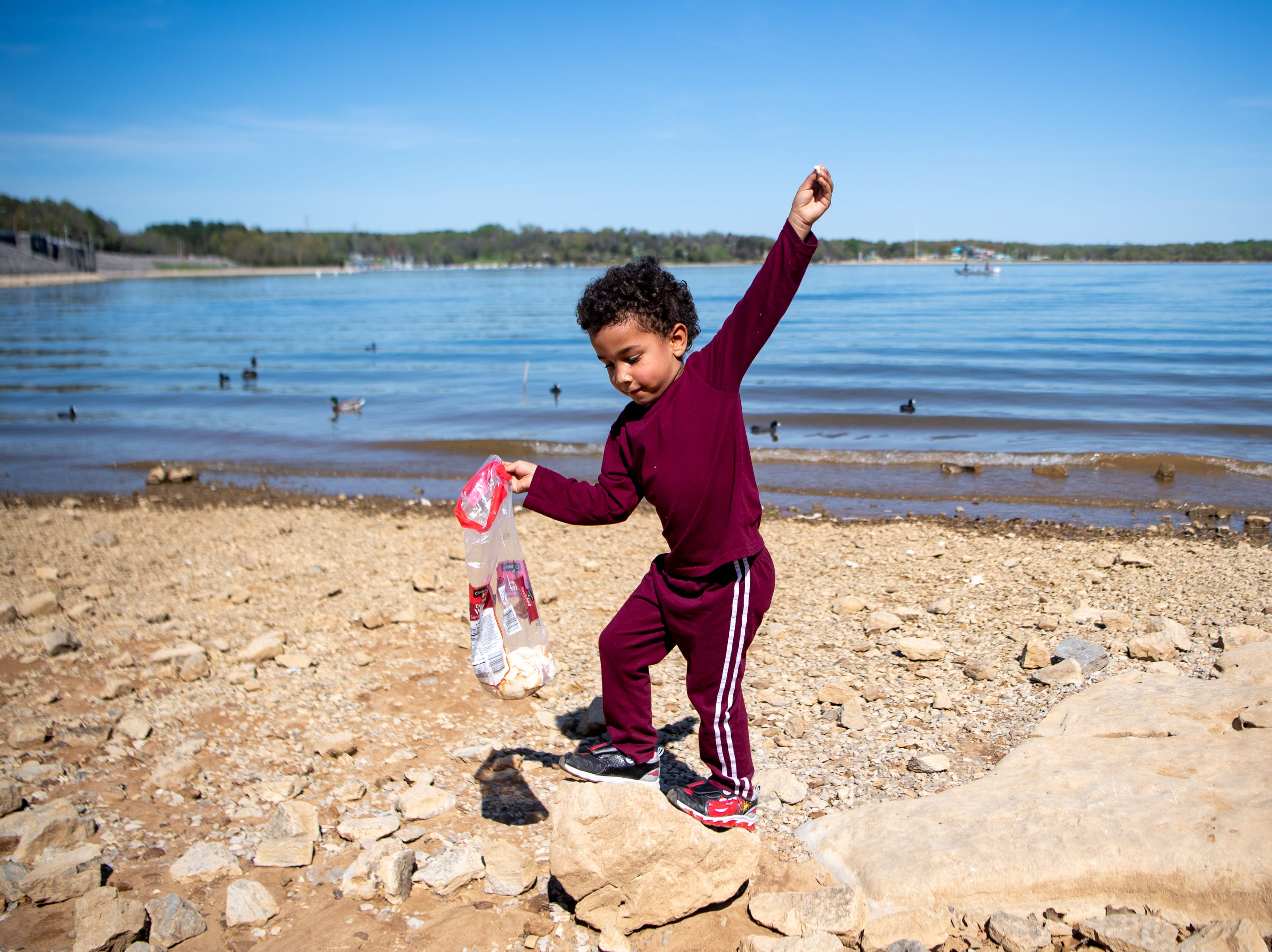 Roosevelt Covington, 5, tries to keep balance on rocks at Percy Priest Lake Wednesday, April 10, 2019, in Nashville, Tenn.