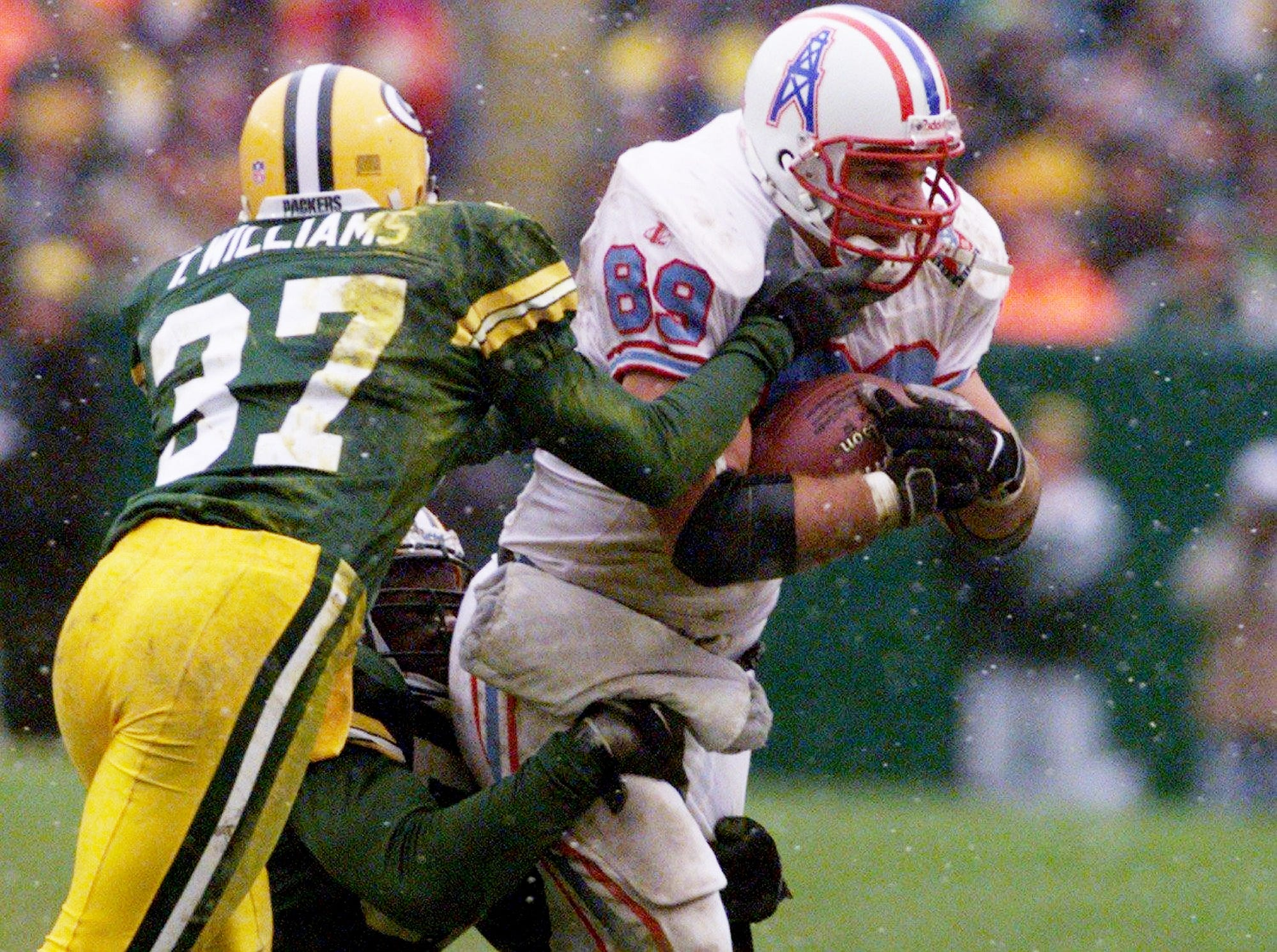 Frank Wycheck (89) of the Tennessee Oilers reaches for extra yards as Tyrone Williams (37) and Brian Williams of the Green Bay Packers push him out of bounds during the 4th quarter. The Oilers lost 30-22 to the Packers on the road Dec. 20, 1998.