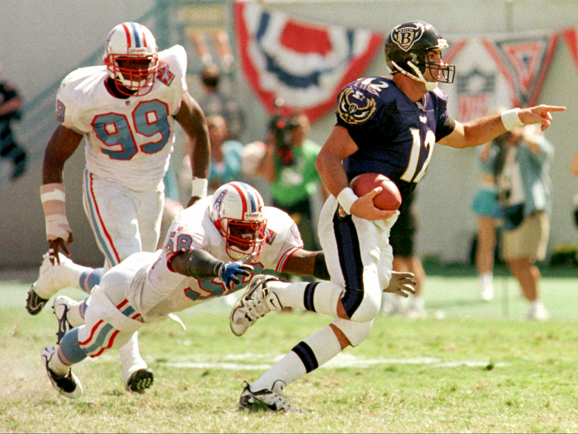 Baltimore Ravens quarterback Vinny Testaverde (12) signals to a teammate before being brought down by the Tennessee Oilers defender Joe Bowden (58) during the Ravens' 36-10 win Sept. 21, 1997 in Memphis. Testaverde threw for 318 yards and three touchdowns. At left is Kenny Holmes (99) of the Oilers.