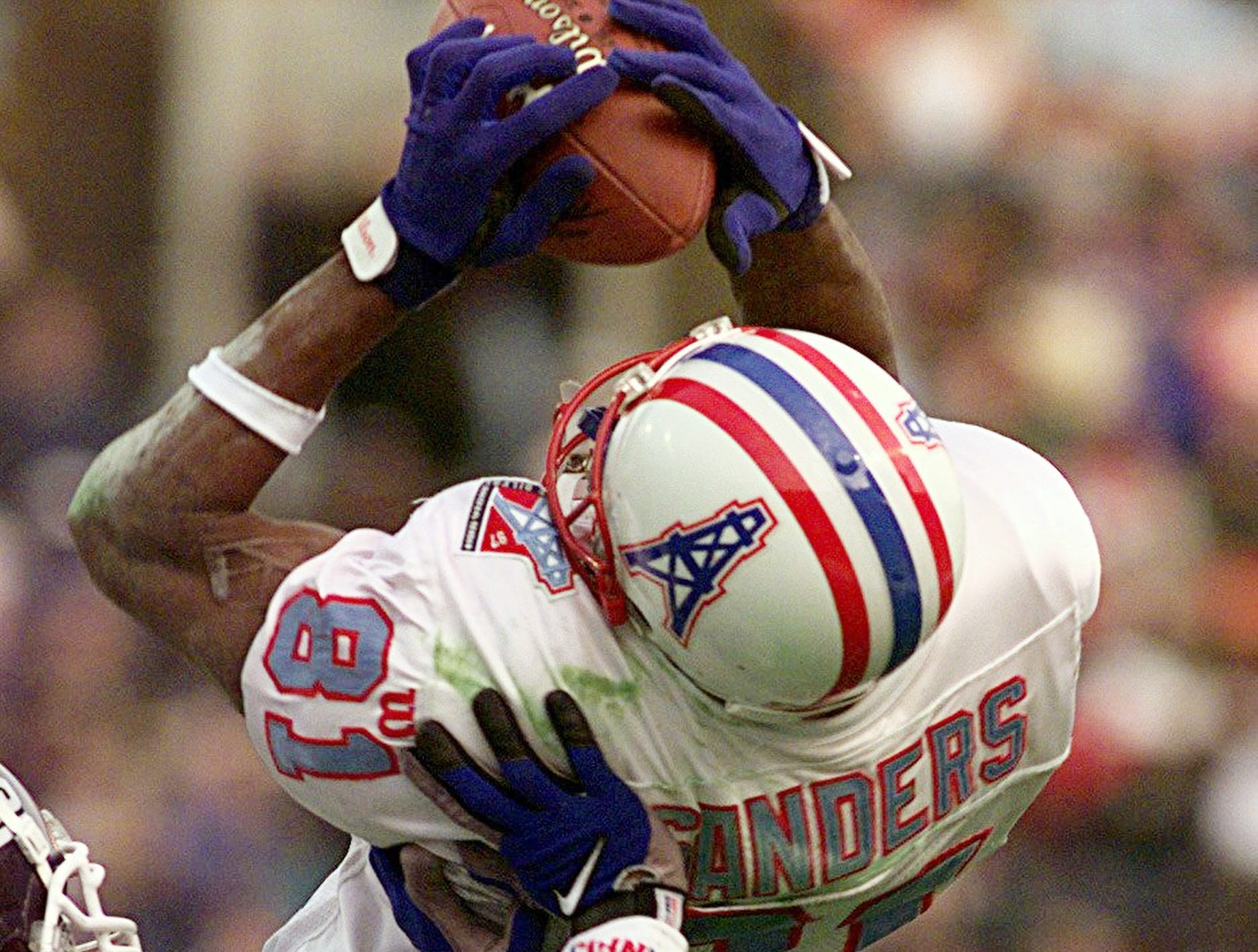 The Tennessee Oilers wide receiver Chris Sanders hauls down a pass in front of the Giants defender Jason Sehorn in the second quarter of their 10-6 victory over New York Nov. 9, 1997.