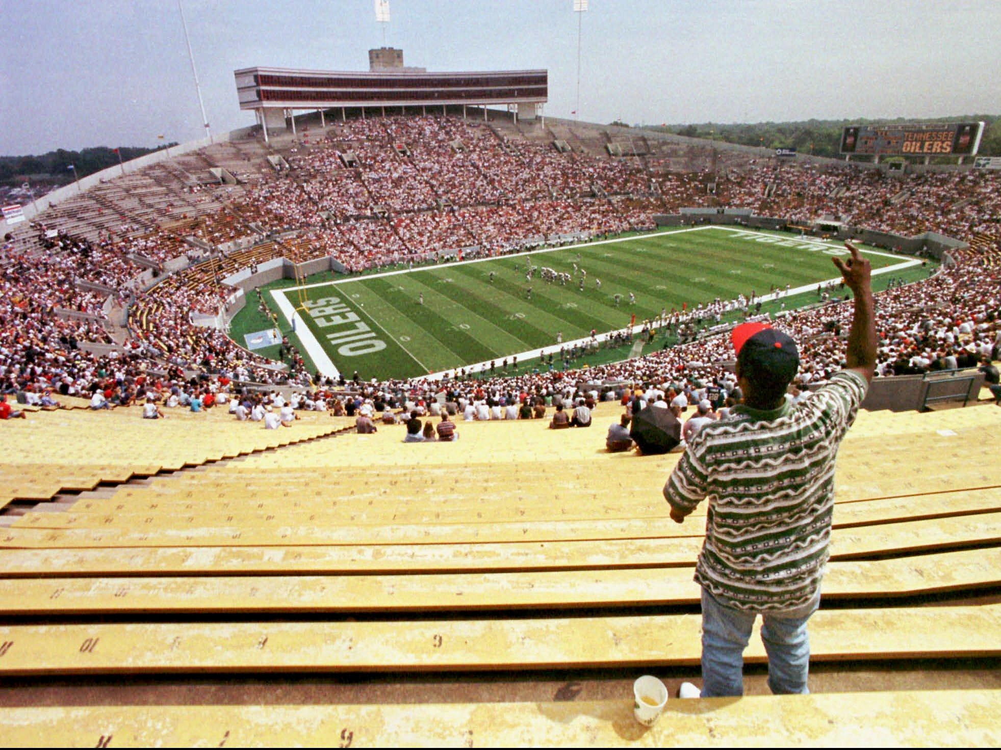 A lone fan surrounded by empty seats cheers on the Tennessee Oilers at their opening game against the Oakland Raiders at Liberty Bowl Stadium in Memphis on Aug. 31, 1997. The Oilers drew an NFL-low crowd of 30,171 fans for the game, less than half the capacity of the stadium.