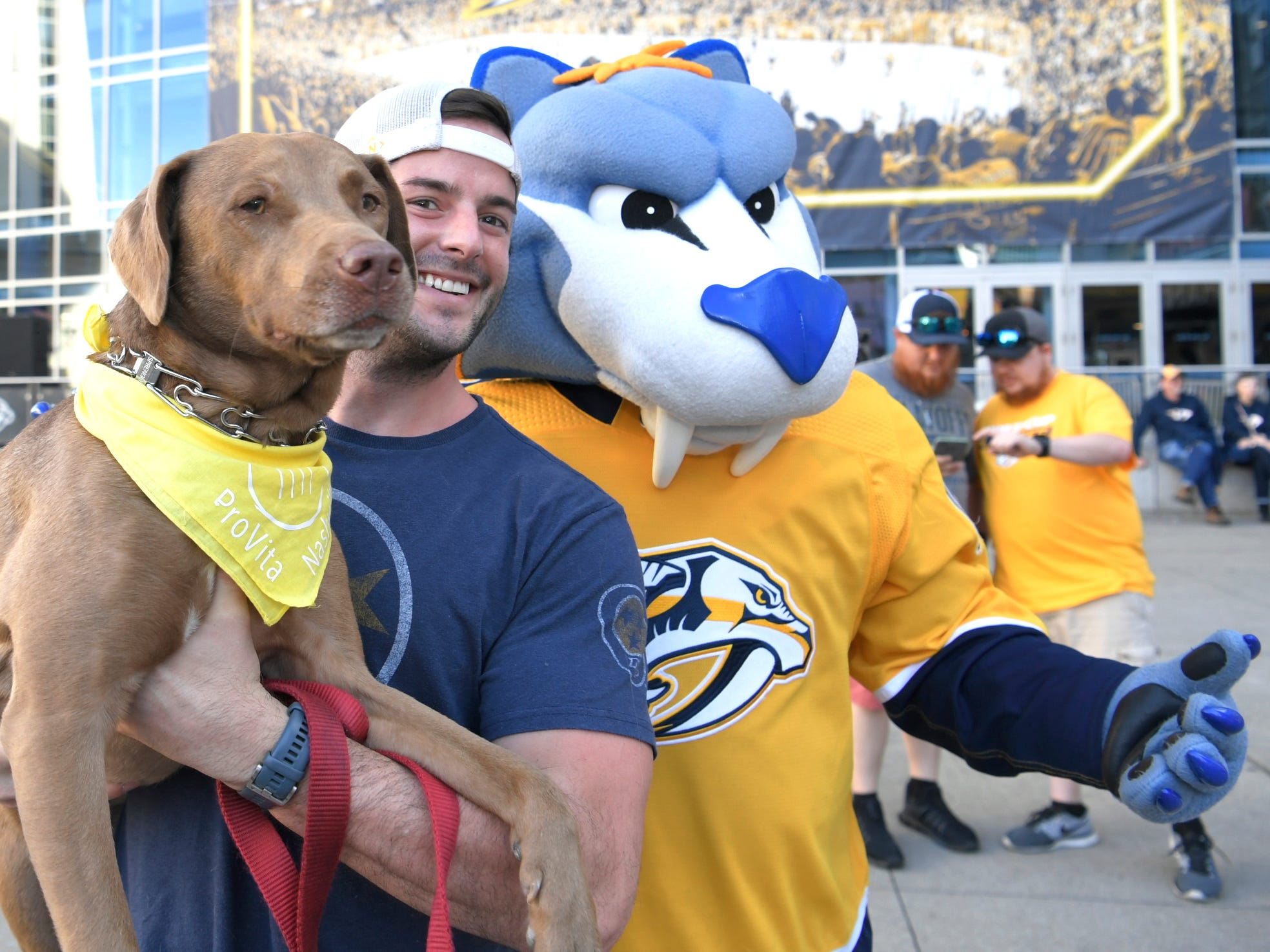 T.J. Faust holds his dog Carter while posing with Gnash before the Predators' divisional semifinal game at Bridgestone Arena in Nashville, Tenn., Wednesday, April 10, 2019.