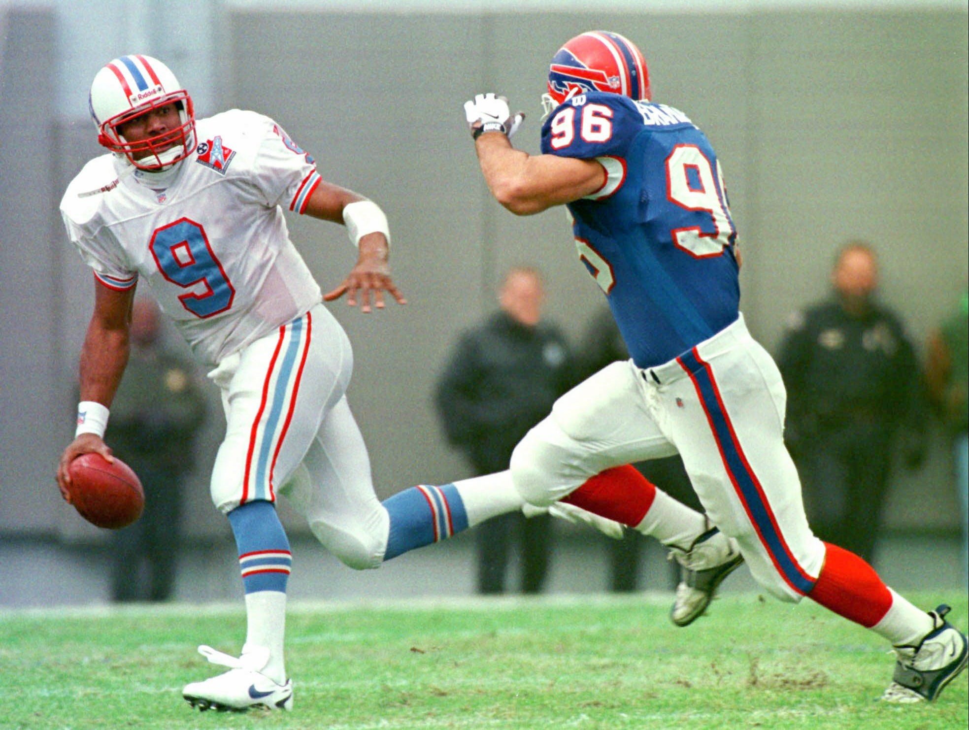 Tennessee Oilers quarterback Steve McNair (9) scrambles from Buffalo Bills linebacker Dan Brandenburg (96) in the first quarter of the Oilers' 31-14 win Nov. 23, 1997 in Memphis. McNair threw for 167 yards and one touchdown and also ran for two touchdowns.