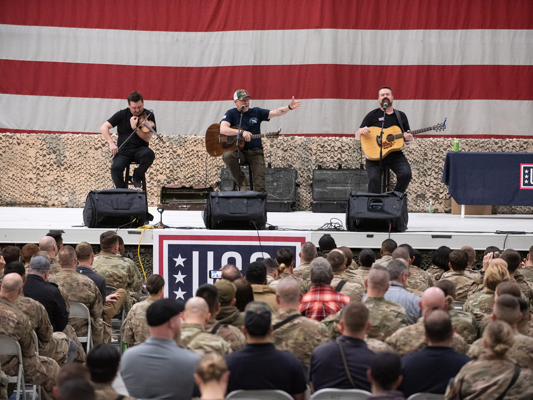 Entertainers and athletes take questions and interact with the audience during a USO Show at Bagram Airfield, Afghanistan; the second stop on the annual Vice Chairman's USO Tour, March 31, 2019. Country music artist Craig Morgan, middle, performs.