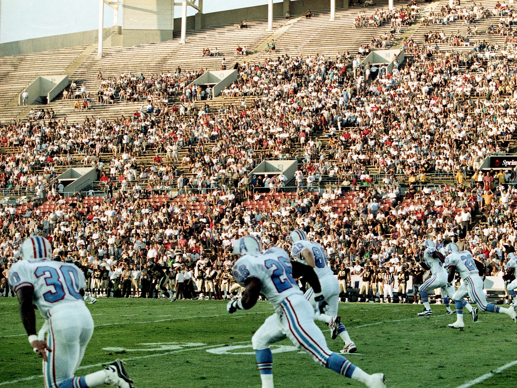 Tennessee Oilers Anthony Dorsett (30), Rayna Stewart (26), Michael Roan (80) and others heads down field on their very first kickoff in their new state Aug. 2, 1997. The Oilers face New Orleans Saints at their temporary home at the Library Bowl in Memphis.