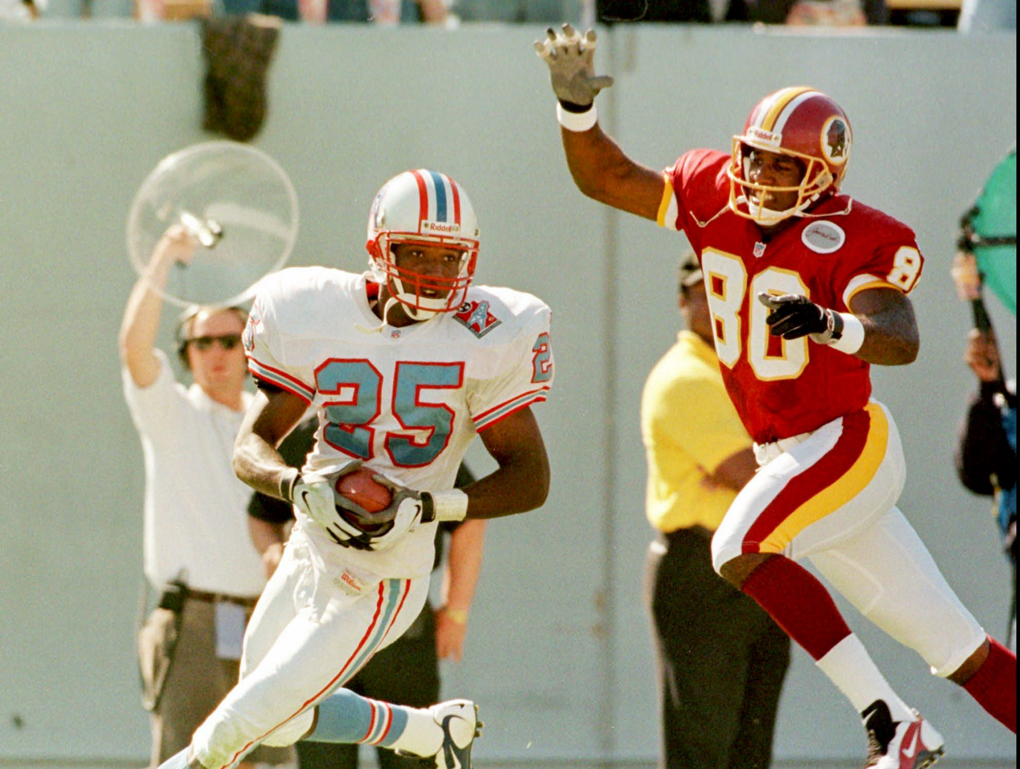 Tennessee Oilers' cornerback Denard Walker (25) runs after intercepting a pass intended for the Redskins' Alvin Harper (80) during the fourth quarter of the Oilers' 28-14 win Oct. 19, 1997 in Memphis. It was the first interception for the Oilers this season.