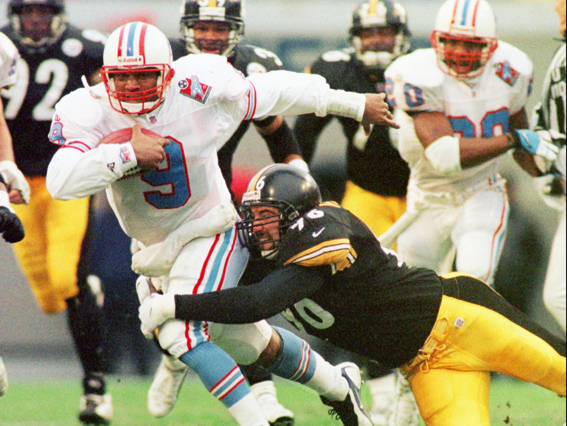 Tennessee Oilers quarterback Steve McNair (9) is brought down by Pittsburgh Steelers defender Mike Vrabel (96) after a 12-yard gain by McNair in the second quarter of the Oilers' 16-6 win Dec. 21, 1997 in Memphis. McNair passed for 102 yards and was the team's leading rusher with 90 yards.