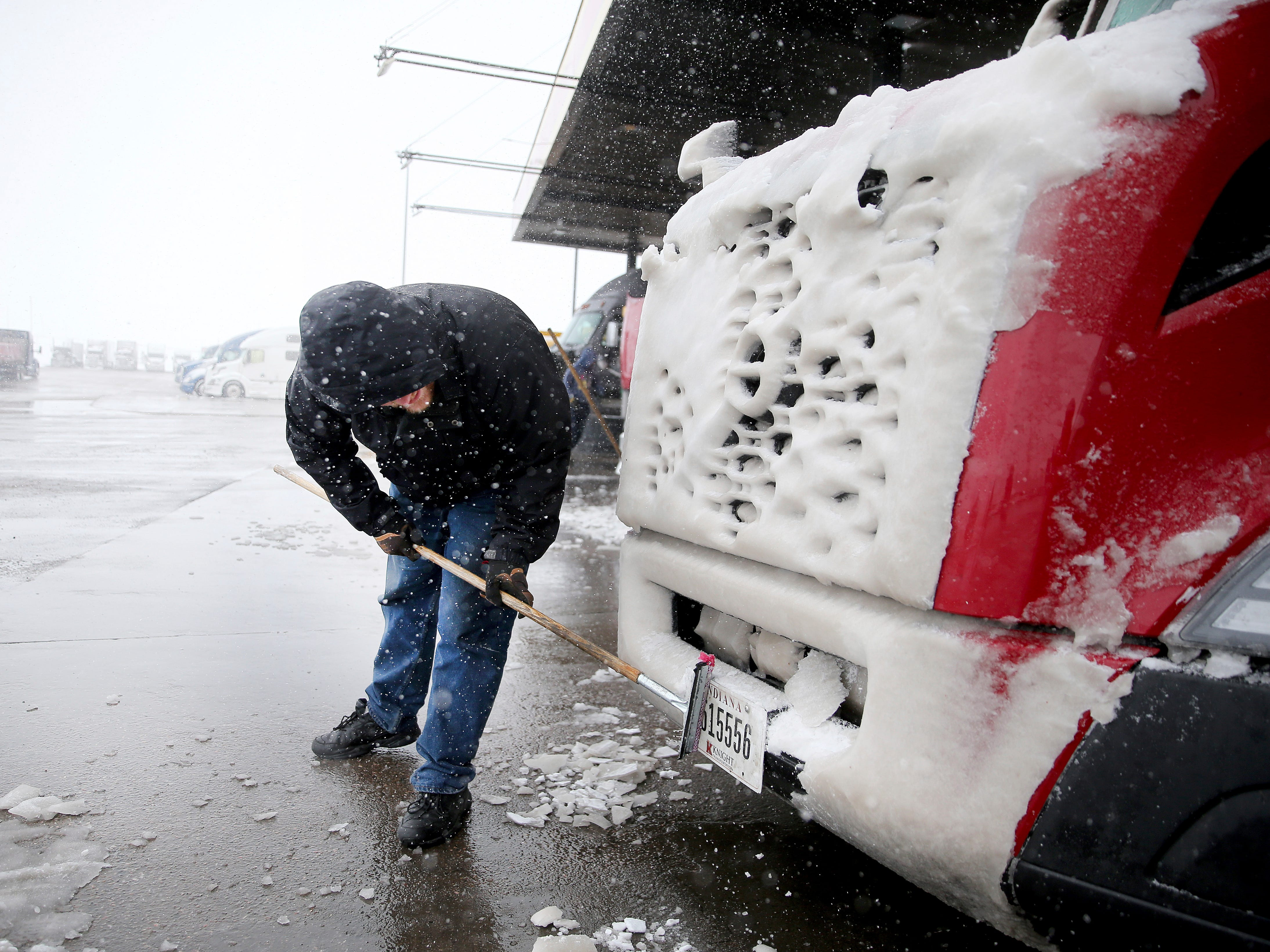 Alan Brown of Colorado Springs, Colo., attempts to clear ice from his truck's license plate as he prepares to continue the trek to Billings, Mont., while passing through Love's Travel Stop during a blizzard warning hitting southeast Wyoming Wednesday, April 10, 2019, in Cheyenne. People in Colorado and Wyoming were urged to get home early Wednesday and stay there before snow and wind from a powerful spring storm make travel all but impossible.