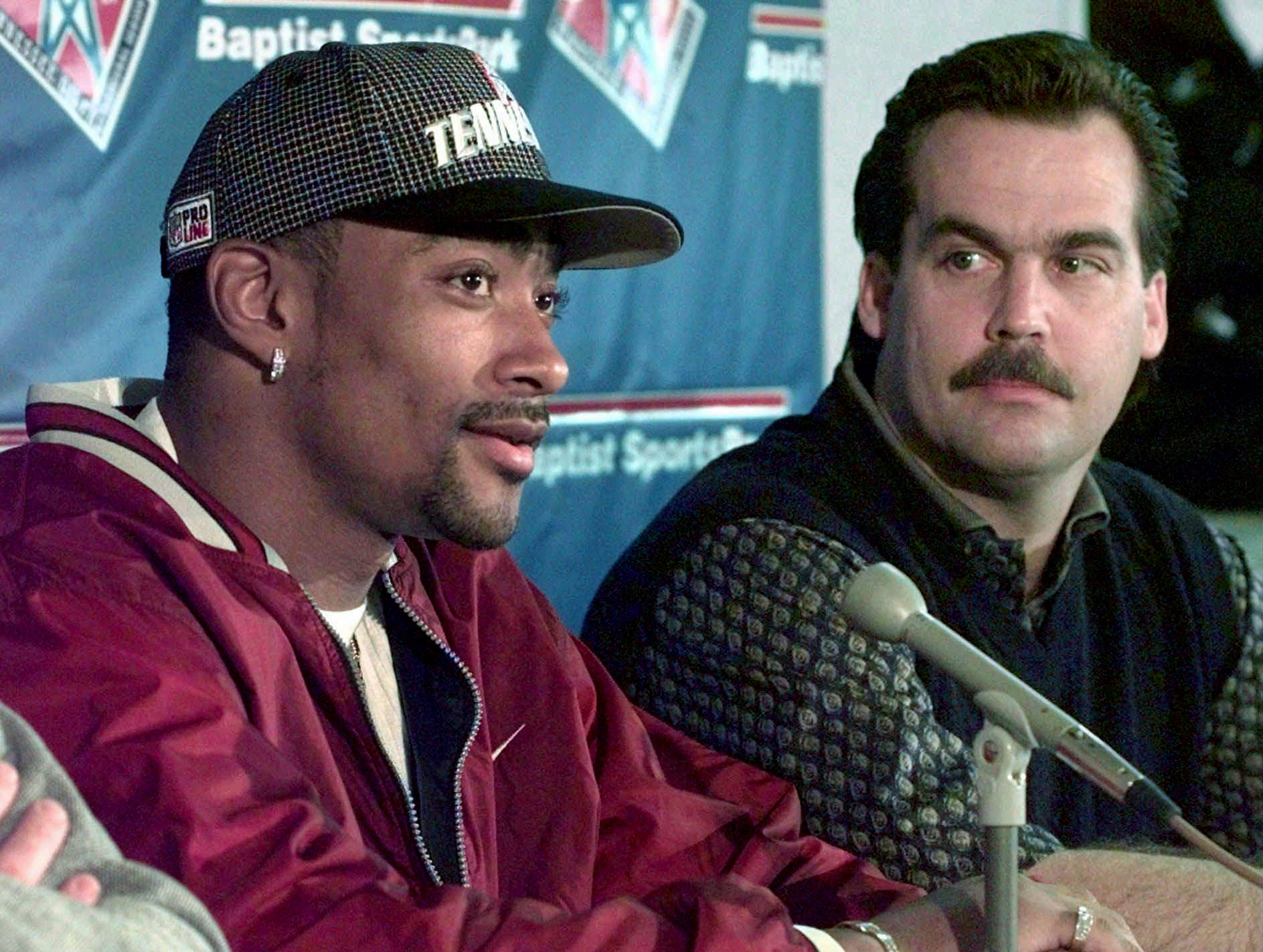 Wide receiver Yancy Thigpen, left, answers questions Feb. 14, 1998 as Tennessee Oilers coach Jeff Fisher looks on during the announcement in Nashville that Thigpen had signed a five-year contract with the Oilers after being formerly with the Pittsburgh Steelers.