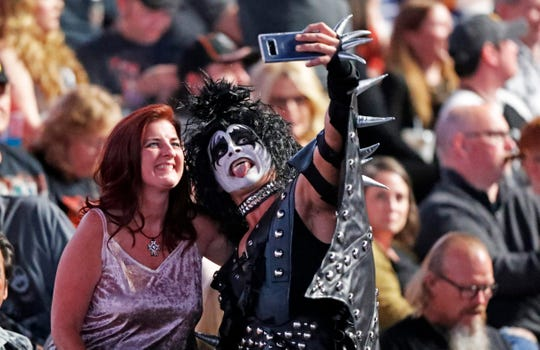 A  KISS fan dressed like Gene Simmons takes a selfie with another fan before their concert at Bridgestone Arena Tuesday, April 9, 2019, in Nashville, TN.