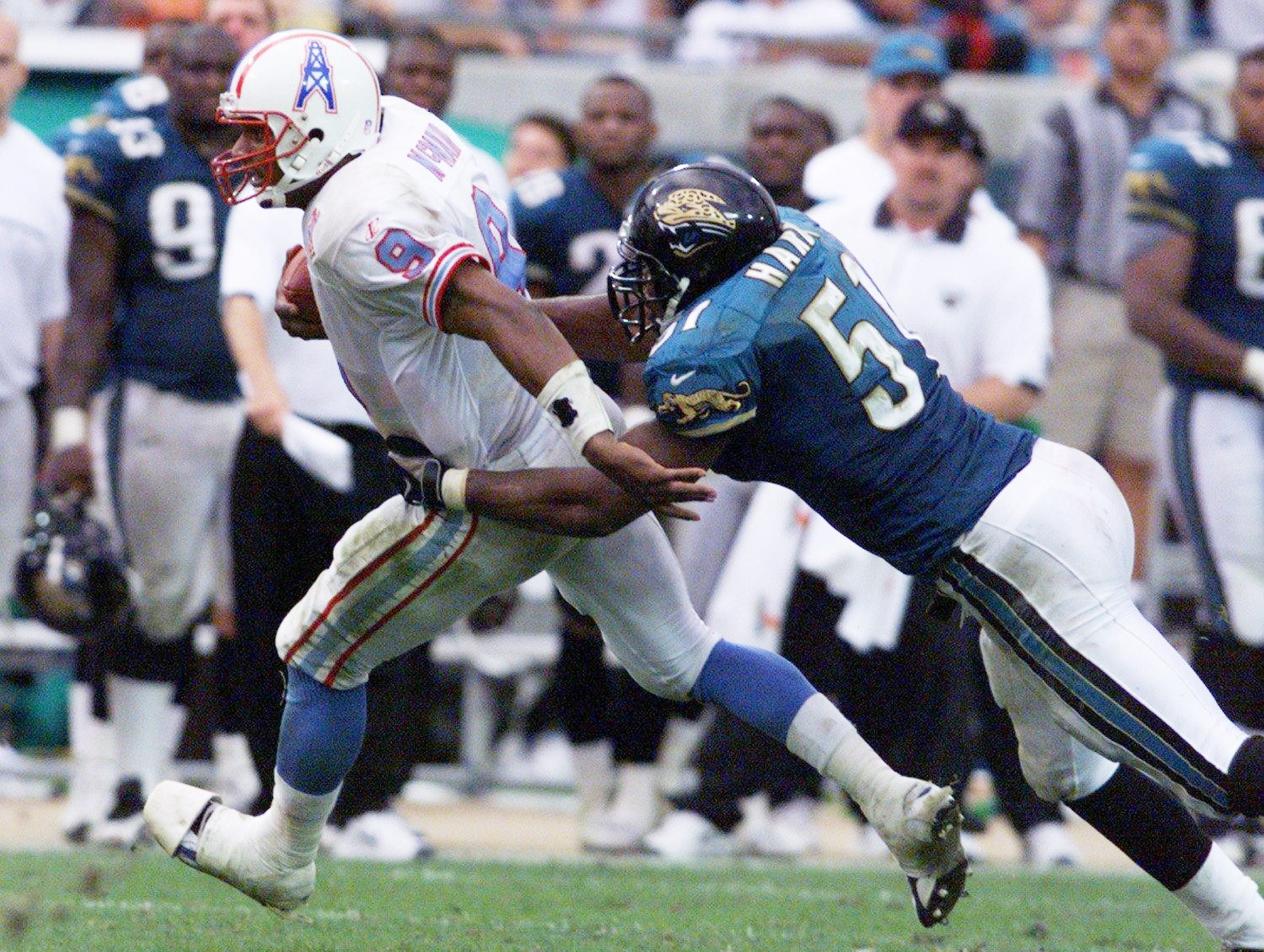 Tennessee Oilers quarterback Steve McNair (9) tries to escape from Kevin Hardy of the Jacksonville Jaguars as he scrambles for yard late in the fourth quarter. The Oilers won the road game 16-13 Dec. 13, 1998.
