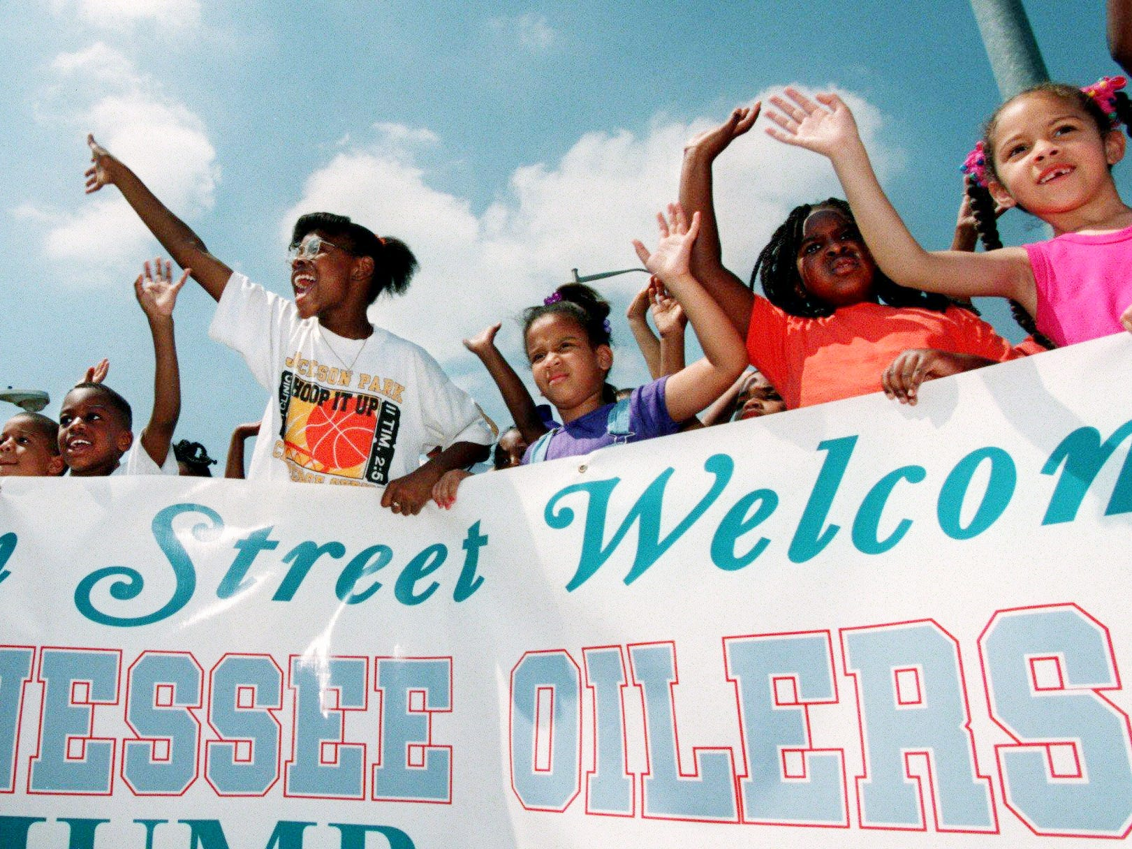 The Tennessee Oilers moving van is greeted by a small pocket of fans at the corner of 23rd Ave. and Jefferson St. July 11, 1997. The vans were moving equipment for the Tennessee Oilers training camp at Tennessee State University, starting July 18th.