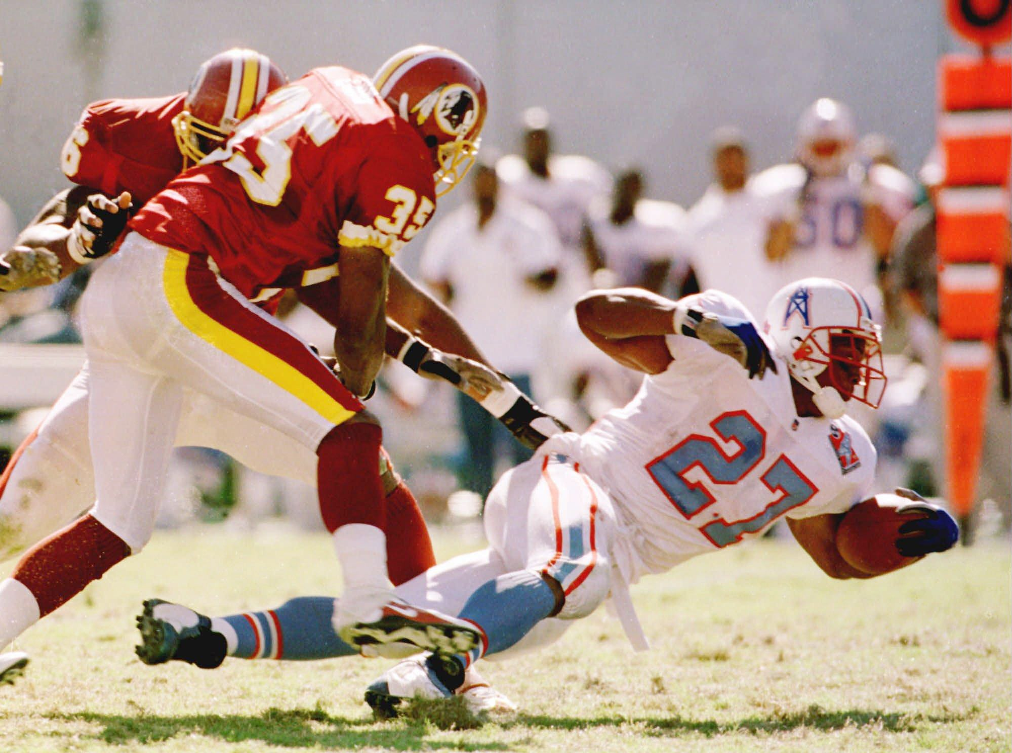 Tennessee Oilers running back Eddie George (27) stretches for a few extra yards as he is brought down by Washington Redskins Leomont Evans (35) during Tennessee's 28-14 win Oct. 19, 1997 in Memphis. George rushed for 125 yards and two touchdowns.