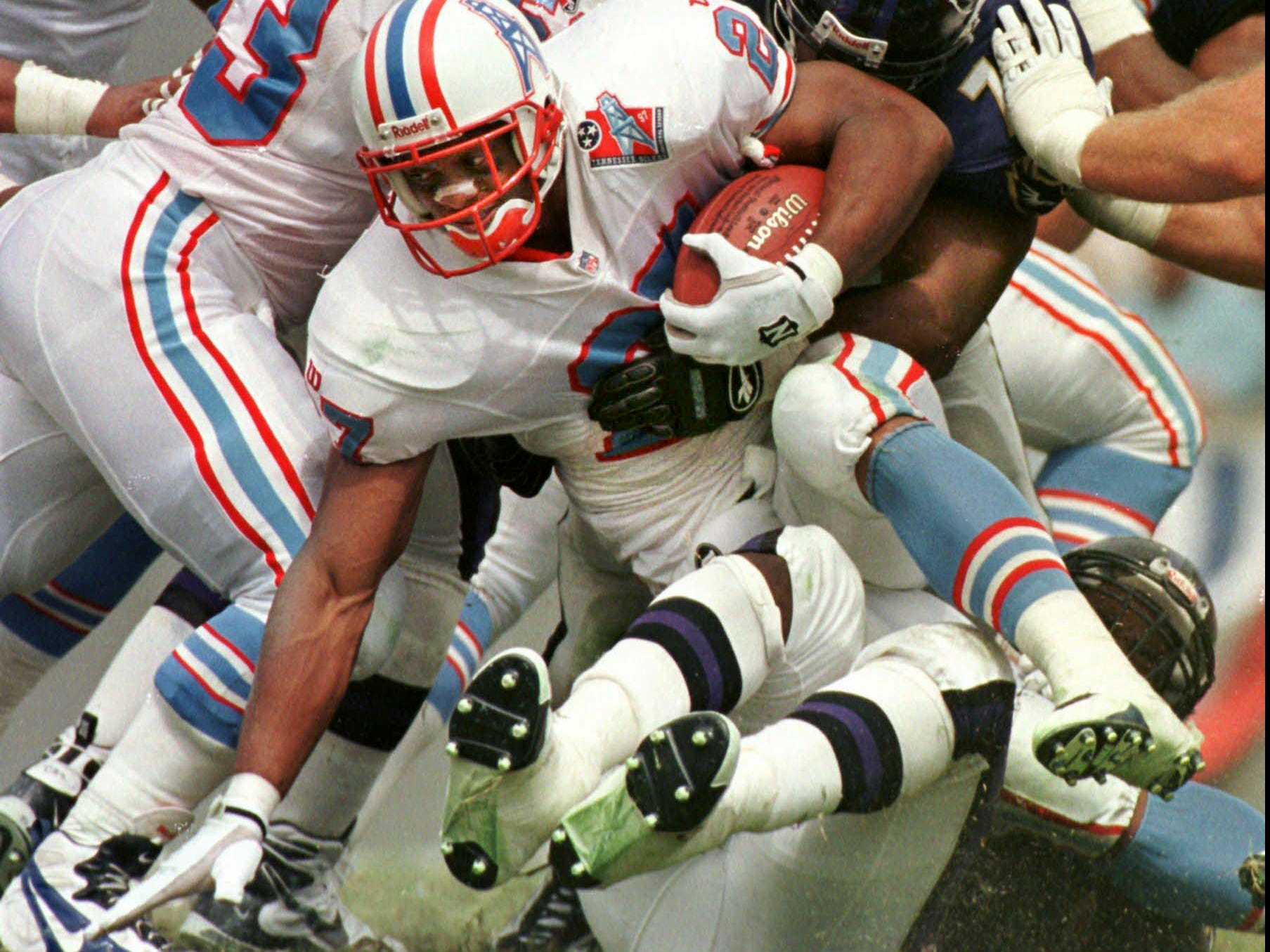 Tennessee Oilers running back Eddie George is stopped by Baltimore Ravens' lineman Larry Webster (79) during the Ravens' 36-10 win Sept. 21, 1997 in Memphis. The Ravens' defense held George to 40 yards rushing for the game.