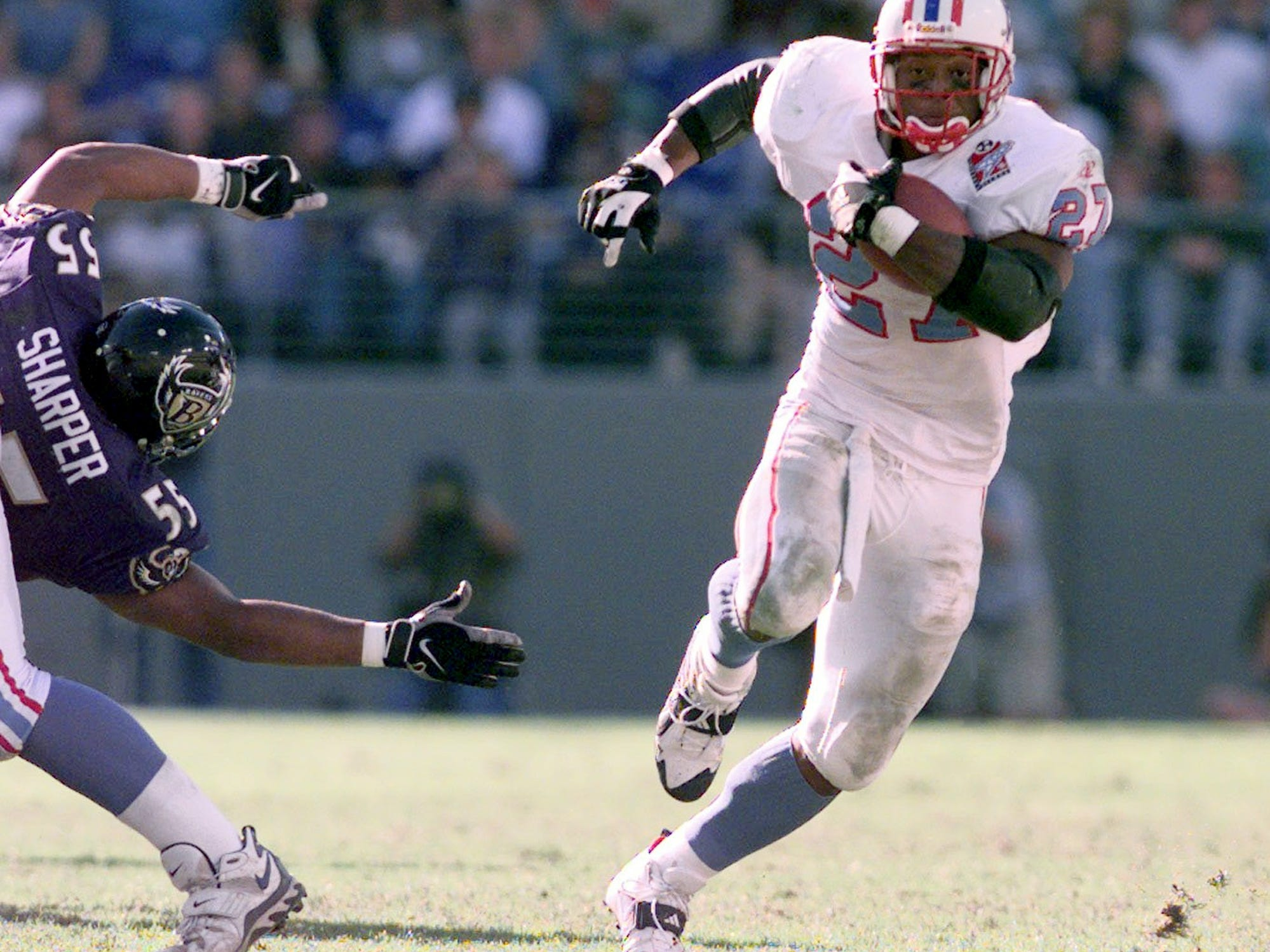 Tennessee Oilers running back Eddie George, right, runs for big yard during the fourth quarter as Jamie Sharper of the Baltimore Ravens reaches for him. The Oilers won the game 12-8 on the road Oct. 11, 1998.