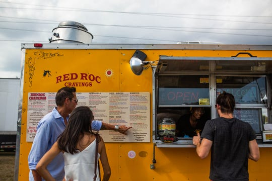 Customers order at Red Roc Cravings, one of a dozen food trucks at the Naples City Live event on April 6.