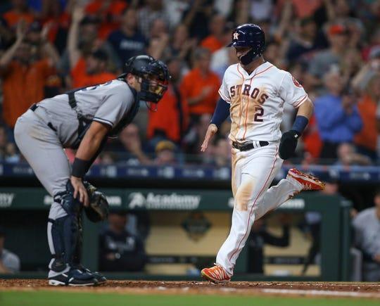 Apr 9, 2019; Houston, TX, USA; Houston Astros third baseman Alex Bregman (2) scores a run as New York Yankees catcher Austin Romine (28) looks on during the seventh inning at Minute Maid Park.