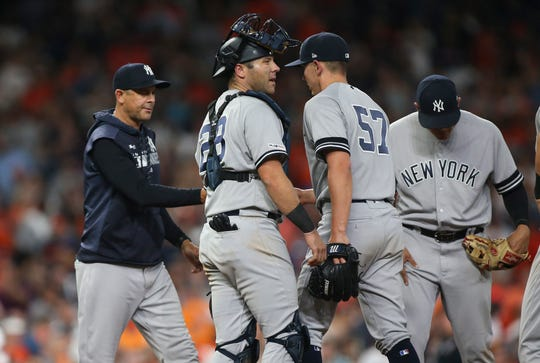 Apr 9, 2019; Houston, TX, USA; New York Yankees relief pitcher Chad Green (57) hands the ball to manager Aaron Boone (17) during a pitching change in the eighth inning against the Houston Astros at Minute Maid Park.