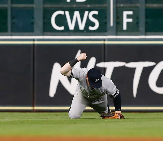 Clint Frazier of the New York Yankees pounds his fist into the field after not being able to catch a line drive off the bat of Michael Brantley of the Houston Astros that ended up as double in the seventh inning at Minute Maid Park on April 09, 2019 in Houston, Texas.