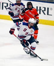 In this Wednesday, Nov. 21, 2018, photo, Jack Hughes, foreground, expected to be a top pick in the next NHL hockey draft, plays against Bowling Green in Plymouth, Mich. USA Hockey has developed the nation's top players for more than two-plus decades, producing a quartet of No. 1 overall picks in the NHL draft, including Auston Matthews and Patrick Kane. Hughes may be next. (AP Photo/Carlos Osorio)