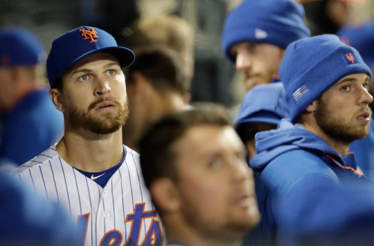 New York Mets starting pitcher Jacob deGrom looks at the scoreboard from the dugout after leaving the fourth inning of an interleague baseball game against the Minnesota Twins, Tuesday, April 9, 2019, in New York. deGrom allowed six runs in four innings before leaving the game.