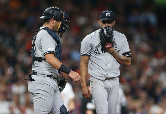 Apr 9, 2019; Houston, TX, USA; New York Yankees catcher Austin Romine (28) talks with starting pitcher Jonathan Loaisiga (38) on the mound during the second inning against the Houston Astros at Minute Maid Park.