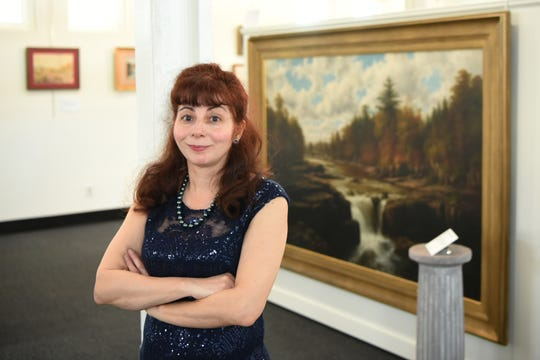 Roxanne Cammilleri, the director of the Clifton Arts Center and Sculpture Park, in front of the painting of the now gone Little Falls on April 10, 2019.