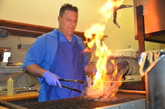 Cactus Cafe owner Dave Mosier fires up the grill as he sears a rib eye steak.
