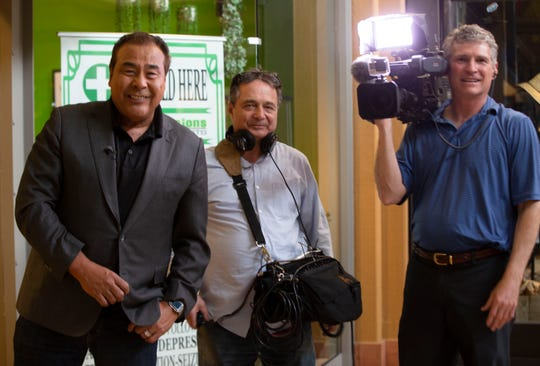 "John Quinones, left, host of the ABC show ""What Would You Do,"" and his film crew — soundman Richie Tropiano, center, and cameraman Carey Mootz — pose for a photo while filming at Mesilla Valley Mall on Thursday, April 4, 2019."