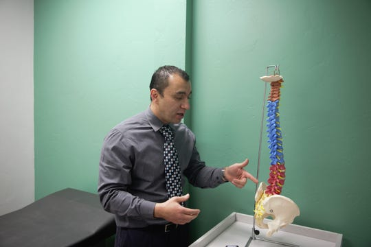 Aaron Villareal explains a fluoroscopy procedure with a model spine in an examining room at the Hygia Pain Institute on April 10, 2019.