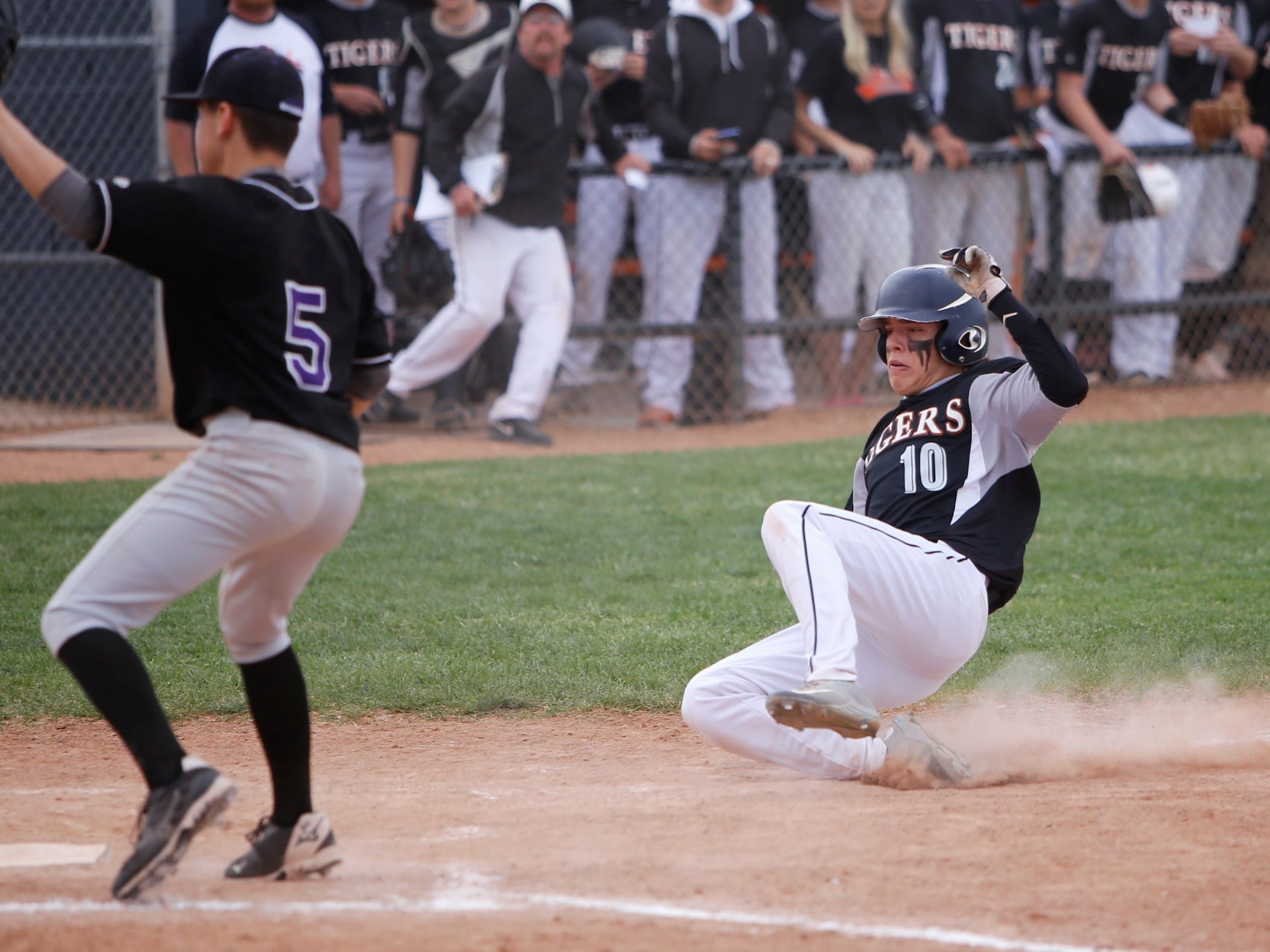Aztec's Derek Jung scores a run off a wild pitch against Miyamura during Tuesday's District 1-4A opener at AHS.