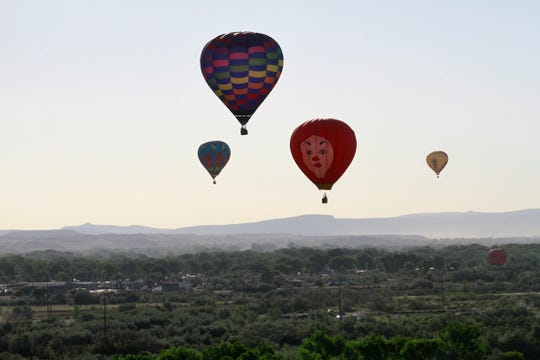 Hot air balloons fly over Bloomfield, Friday, June 17, 2016 during the San Juan River Balloon Rally.