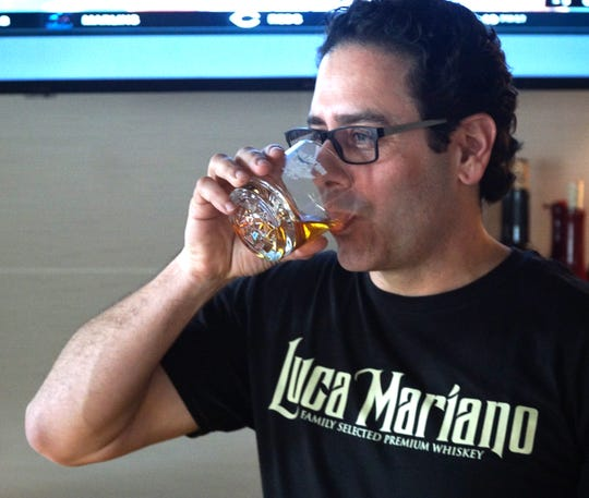 Francesco S. Viola takes a sip of his bourbon - neat - during a visit to Livonia's Cantoro Italian Market on April 10, 2019.