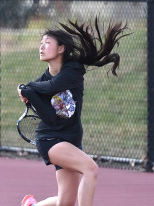 On a windy day in early April #2-ranked Plymouth Wildcat varsity tennis player Allie Zhang lets a shot fly to her Salem High opponent.
