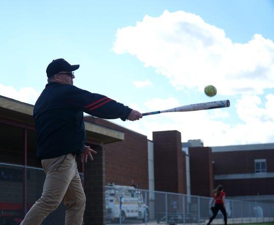 Livonia Churchill softball coach Abe Vinitski hits some fly balls for his team to field.