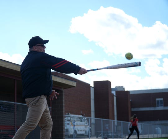 Livonia Churchill softball coach Abe Vinitski hits some fly balls for his team to field.